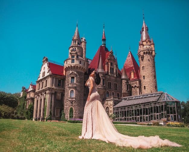 おとぎ話のような中世の城の長いベージュのイブニングドレスの女性。モシュナザメク、ポーランド