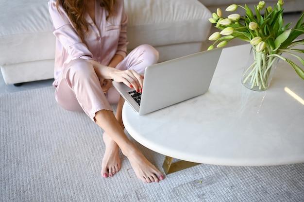 До неузнаваемости женщина в розовой пижаме, сидя на полу, работает на ноутбуке. белый стол с весенними тюльпанами
