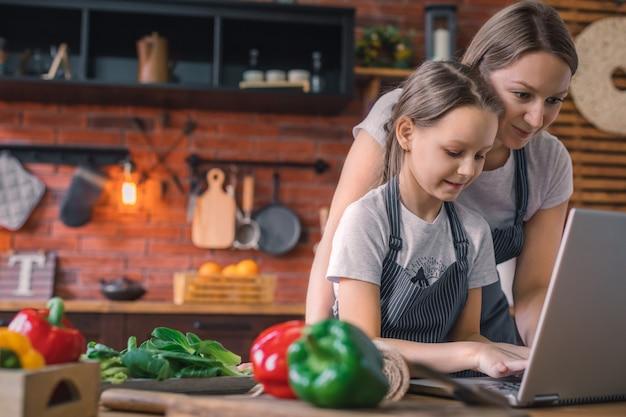 Мама учит дочь готовить тесто