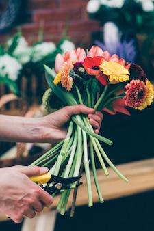 Аранжировщик цветов делает яркий букет