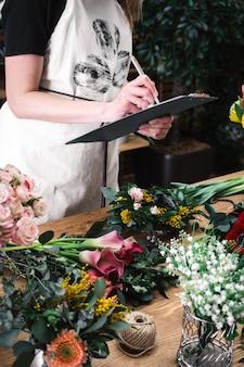 Флорист считает и записывает цветы