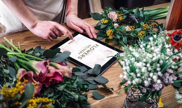 Флорист использует планшет для работы с заказами