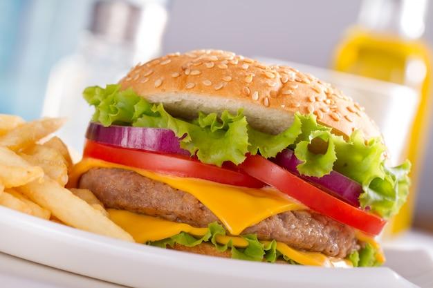 Фаст-фуд есть. бургер и картофель фри на тарелке.