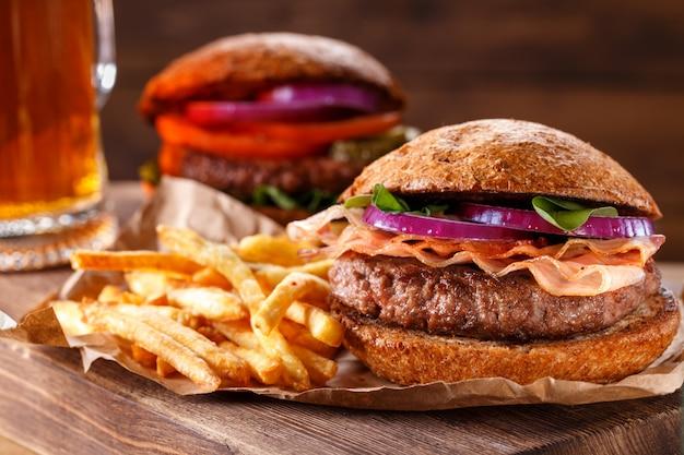 Бургер и картофель фри заделывают на деревянных фоне.