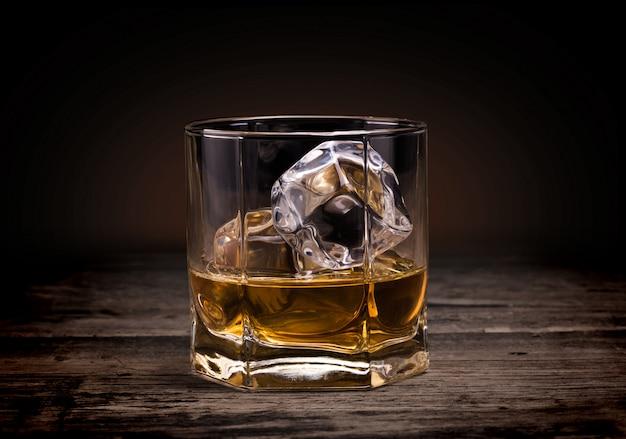 木材の背景にウイスキーのグラス。