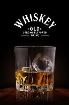 木材の背景にアイスキューブとウイスキーのグラス