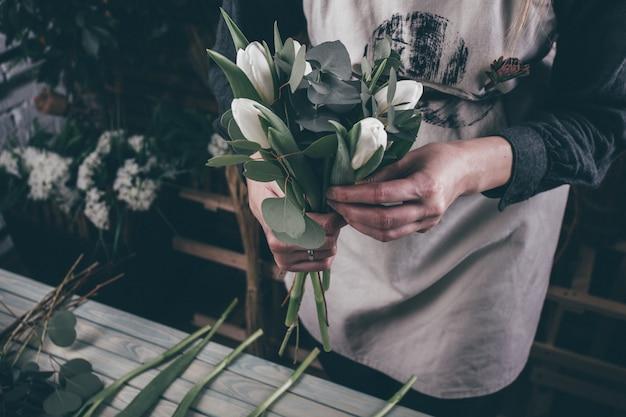 Молодая женщина флорист делает букет красоты