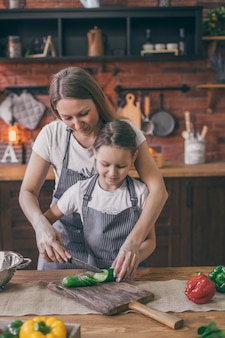 Мать помогает дочери с готовкой