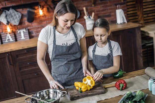 Мать и дочь с перцем на кухне
