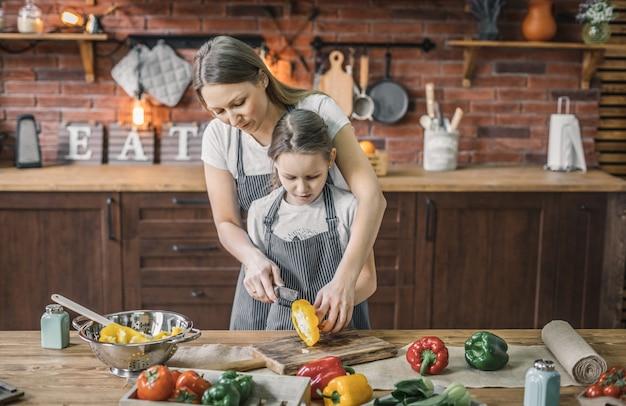 Мать помогает дочери с перцем резки