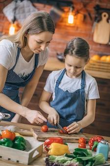 Женщина помогает дочери с помидорами