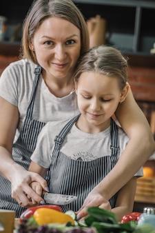 Мать готовит еду с дочерью на кухне