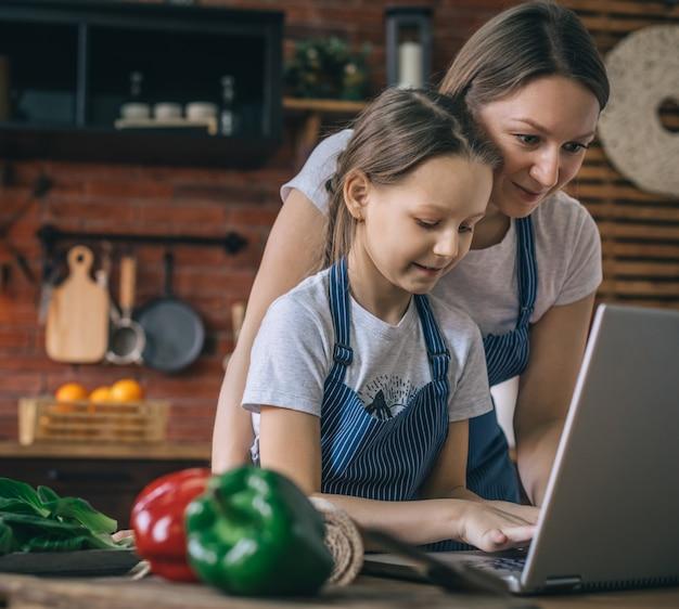 Девушка, набрав на ноутбуке во время приготовления пищи с матерью