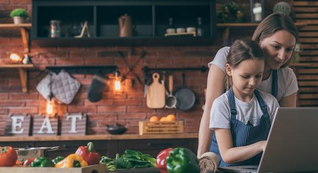Мать и дочь с ноутбуком готовить