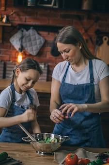 Девушка помогает матери с салатом приправы