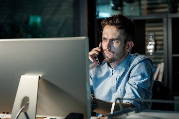 過労と電話で話すオフィスの男
