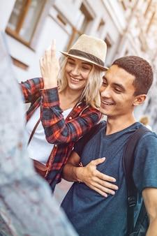 Потерянная молодая пара с картой, улыбаясь на улице