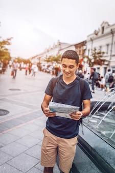 Улыбающийся человек читает газету во время поездки по городу