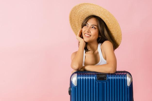 Портрет азиатской женщины в широкополой шляпе и летней одежде, стоящей с чемоданом.