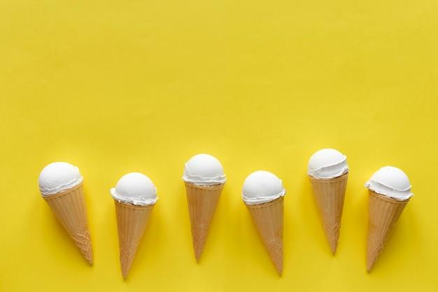 Ряд ванильных конусов мороженого на желтом