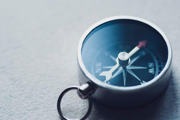 Маленький магнитный компас на сером фоне