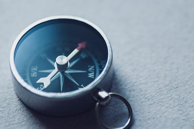 Маленький металлический магнитный компас на текстурированной серой