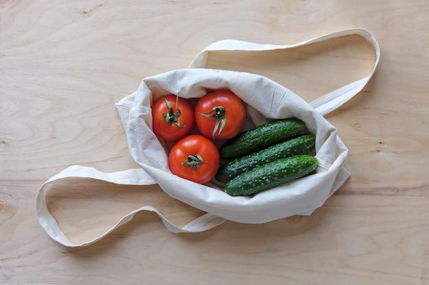 Свежие помидоры и огурцы в матерчатой сумке