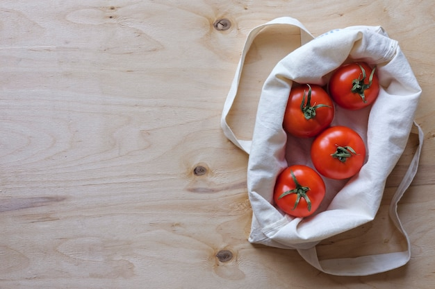 Вид сверху спелых помидоров в тканевой сумке