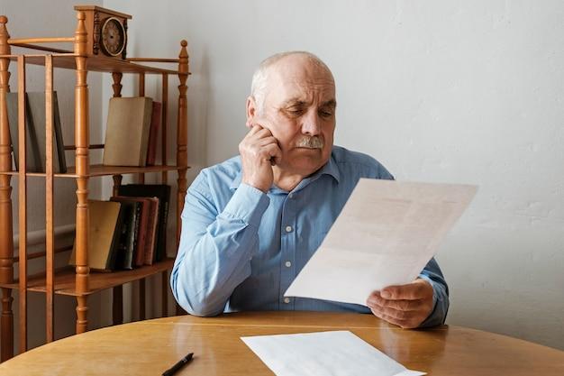 口ひげの読書と高齢者の灰色の髪の男