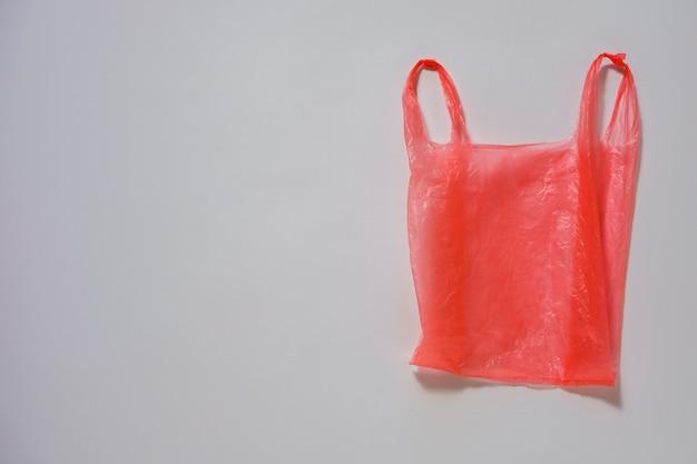 Мятый красный пластиковый пакет на сером