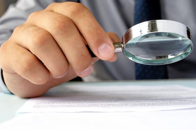 Бизнесмен, глядя через увеличительное стекло на документы