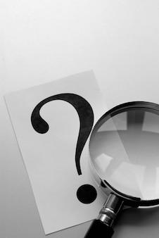 Увеличительное стекло и знак вопроса на бумаге