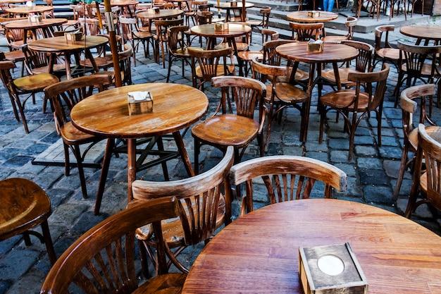Пустые круглые деревянные столы в уличной столовой