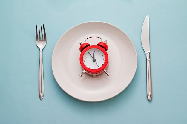 きれいな白いディナープレートに赤い目覚まし時計