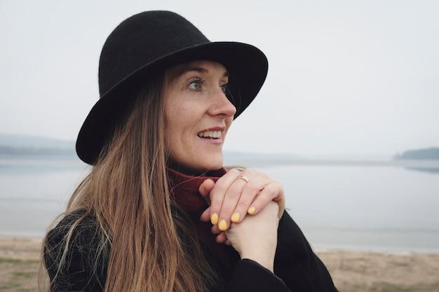 Боковой вид портрет женщины в черной шляпе