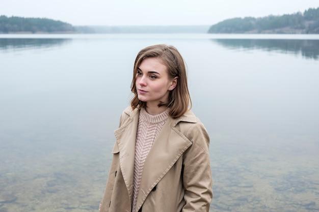 Красивая молодая женщина, стоящая возле озера