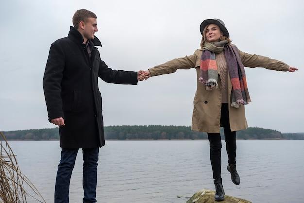 Радостная молодая пара зимой на берегу озера