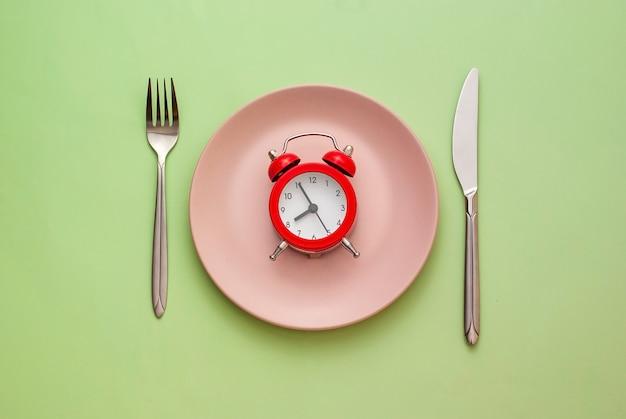 Красный будильник на чистой розовой тарелке