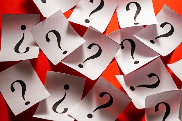 Случайно разбросанные знаки вопроса на белой бумаге