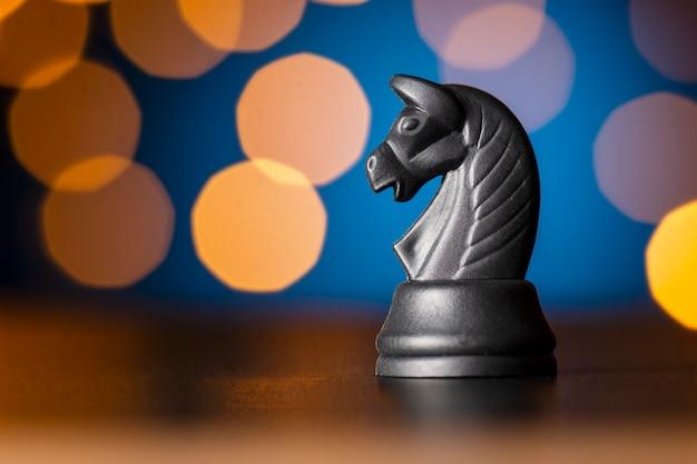Черная лошадь шахматная фигура над красочным боке