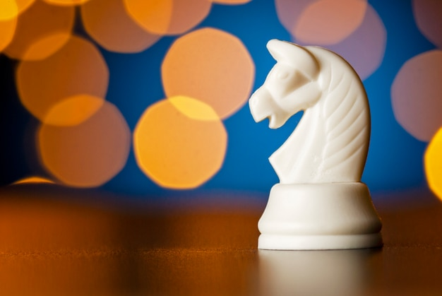 Белая лошадь шахматная фигура над красочным боке