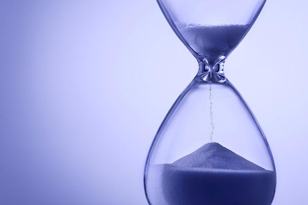 Песочные часы синего цвета с бегущим песком