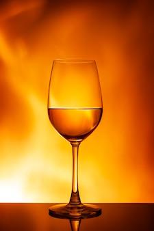 オレンジ色の壁に白ワインのガラス