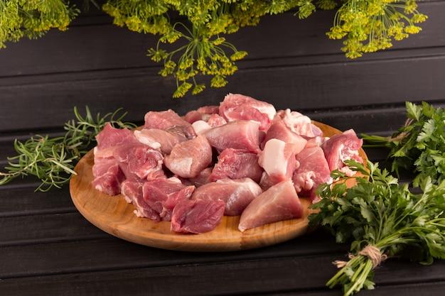 ボード上の牛肉の大きな部分。黒の背景、パセリ。料理レシピの写真