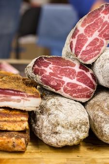 Вяленое мясо разрезается на две части. волокнистая текстура мяса хорошо видна. мясные продукты и сало на прилавке