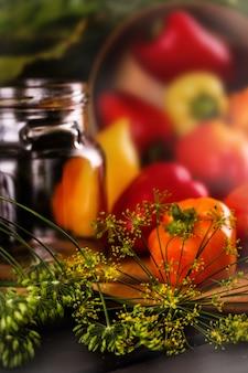 野菜の保存。テーブルの上にはピーマンとディルがあります。空の缶の近く。大きい。