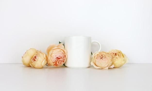 バラと白いコーヒーマグカップ。デザインプロモーションのモックアップの空白のマグカップ。
