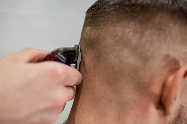 現代の理髪店の残忍な男。美容師は髪型を長いひげを持つ男にします。マスター美容師はバリカンで髪型をします
