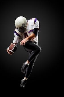 黒のボールでジャンプのアメリカンフットボール選手