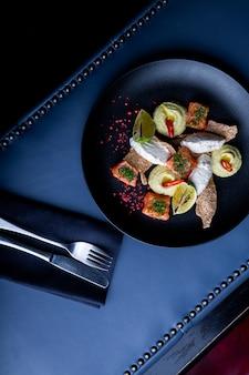 レストランでパテとフムスとおいしいサーモン。大きな黒い大皿のクローズアップで健康的な排他的な食品